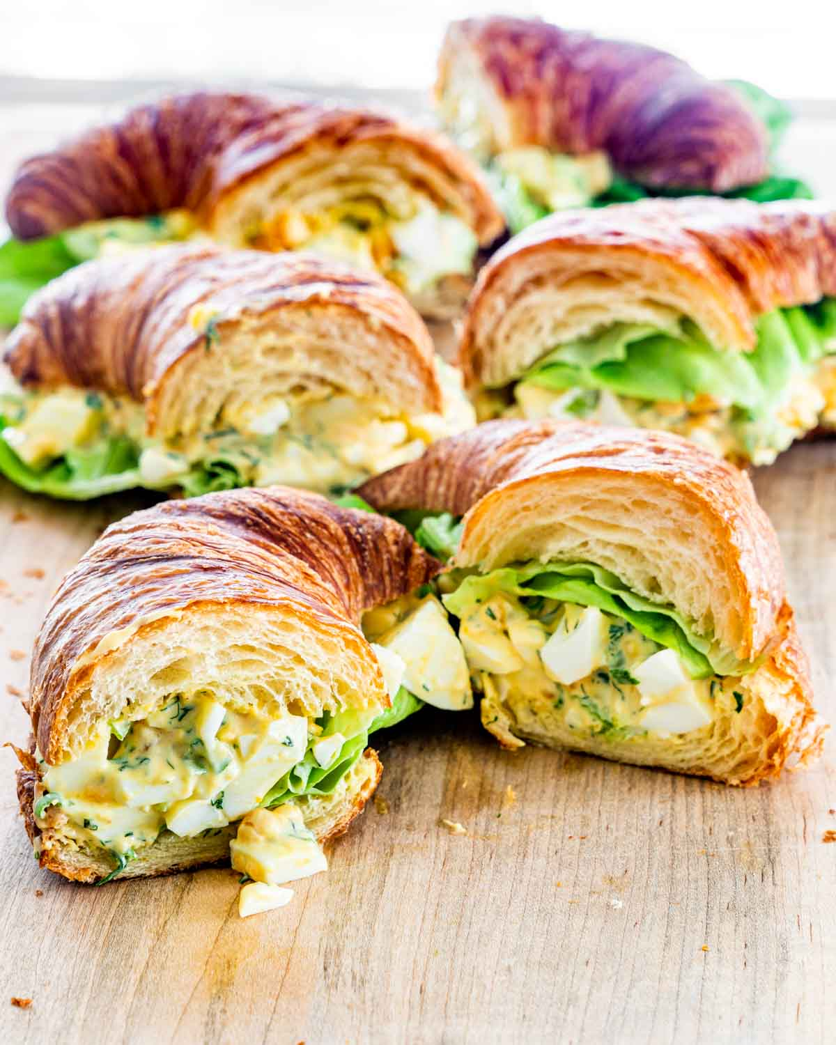 egg salad croissant sandwiches on a cutting board cut in half