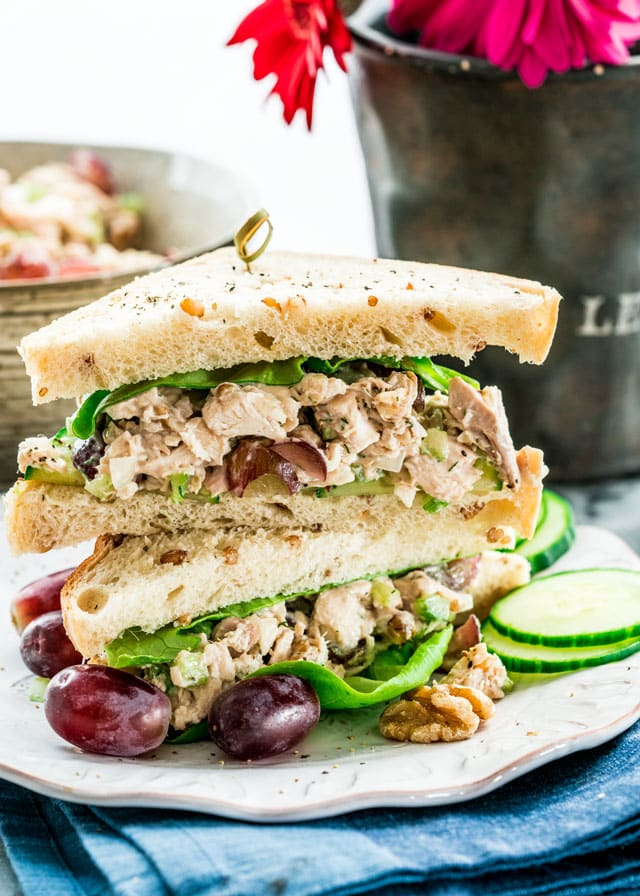 a chicken sandwich cut in half and stacked with grapes and cucumbers