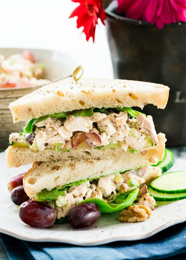 chicken sandwich cut in half and stacked on a plate with grapes and cucumbers