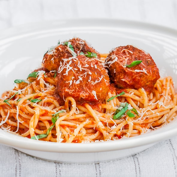 a bowl full of spaghetti topped with three chicken meatballs