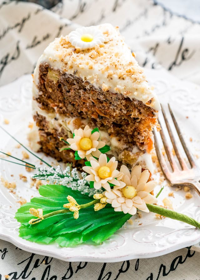 a slice of 2 layer carrot cake on a plate with flowers and a fork