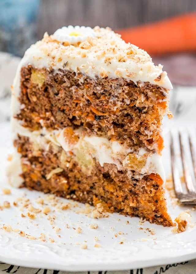 a slice of 2 layer carrot cake with cream cheese icing