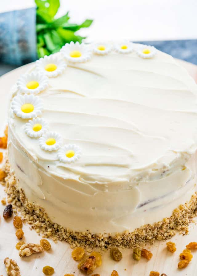 a carrot cake topped with sugar flowers with raisins sprinkled around the outside