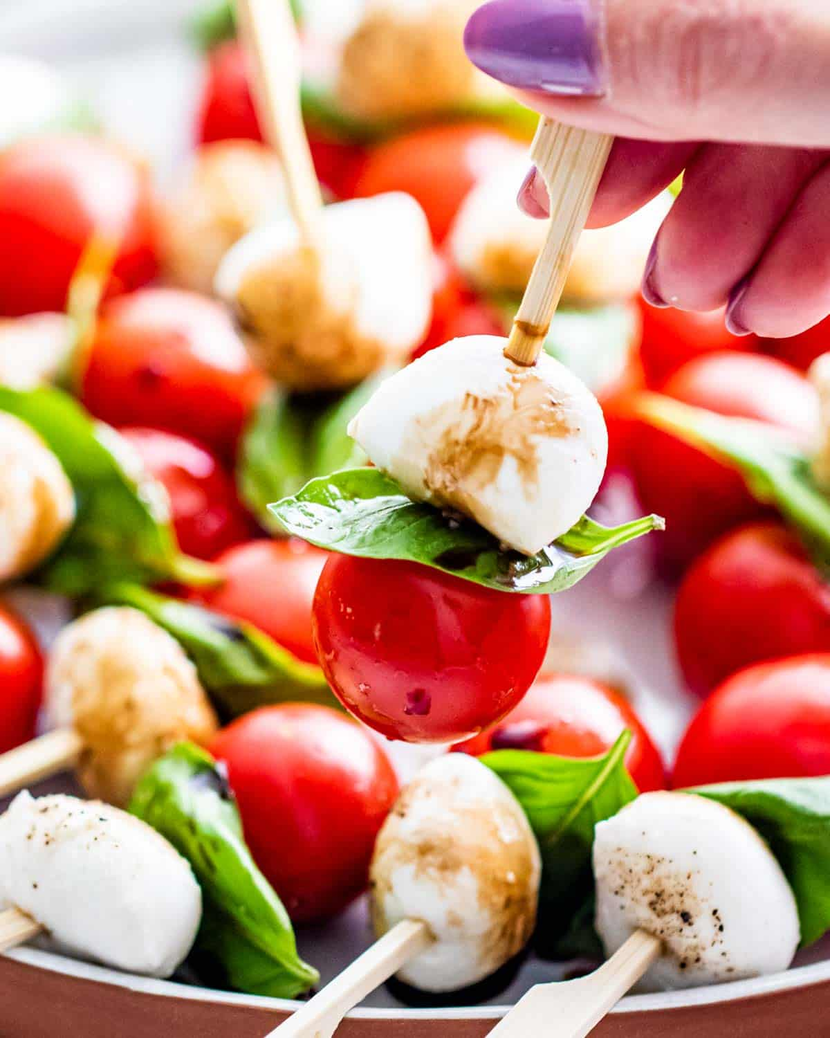 and hand holding a caprese salad bite on a pick over a plate full of them