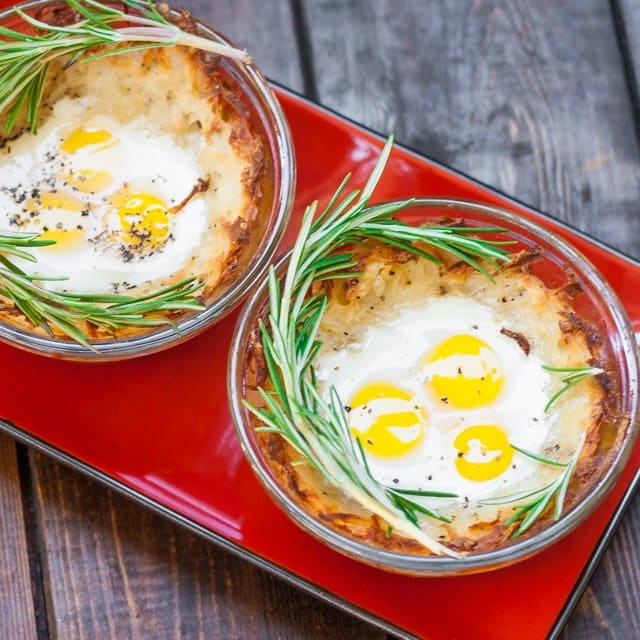two ramekins with Quail Eggs in Hash Brown Nests garnished with fresh rosemary