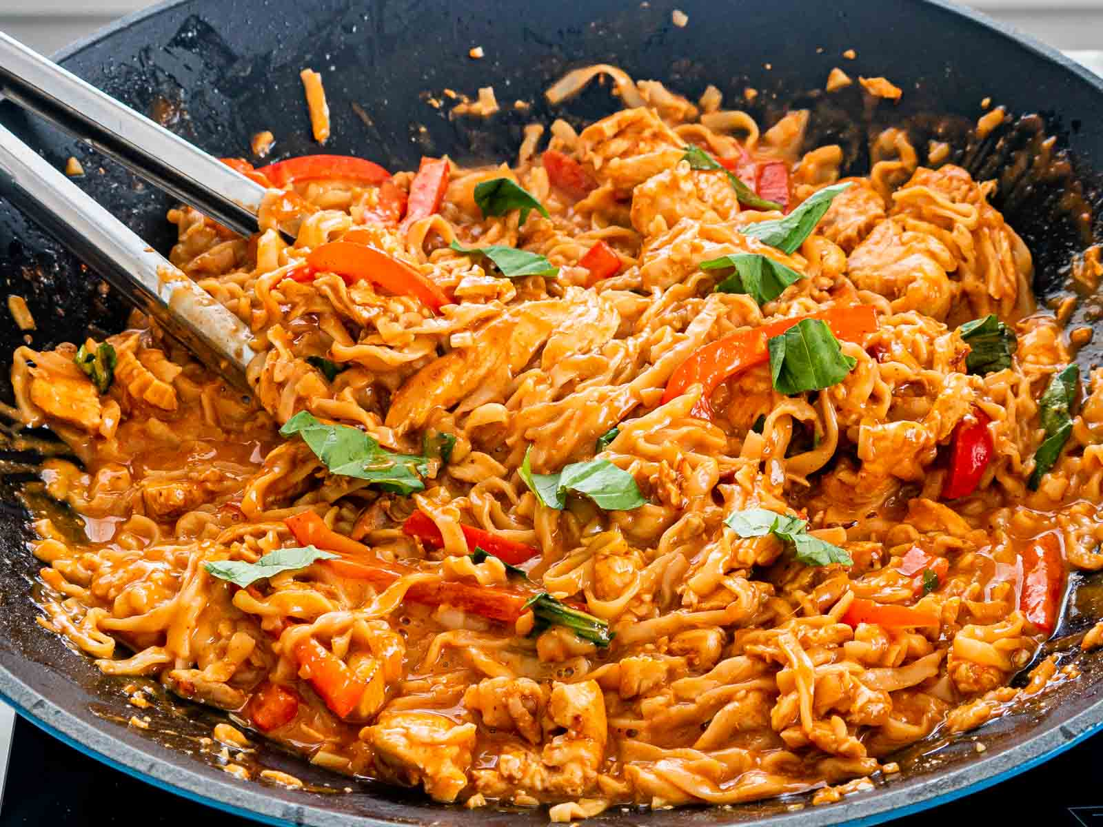 spicy peanut noodles in a wok with a pair of tongs inside