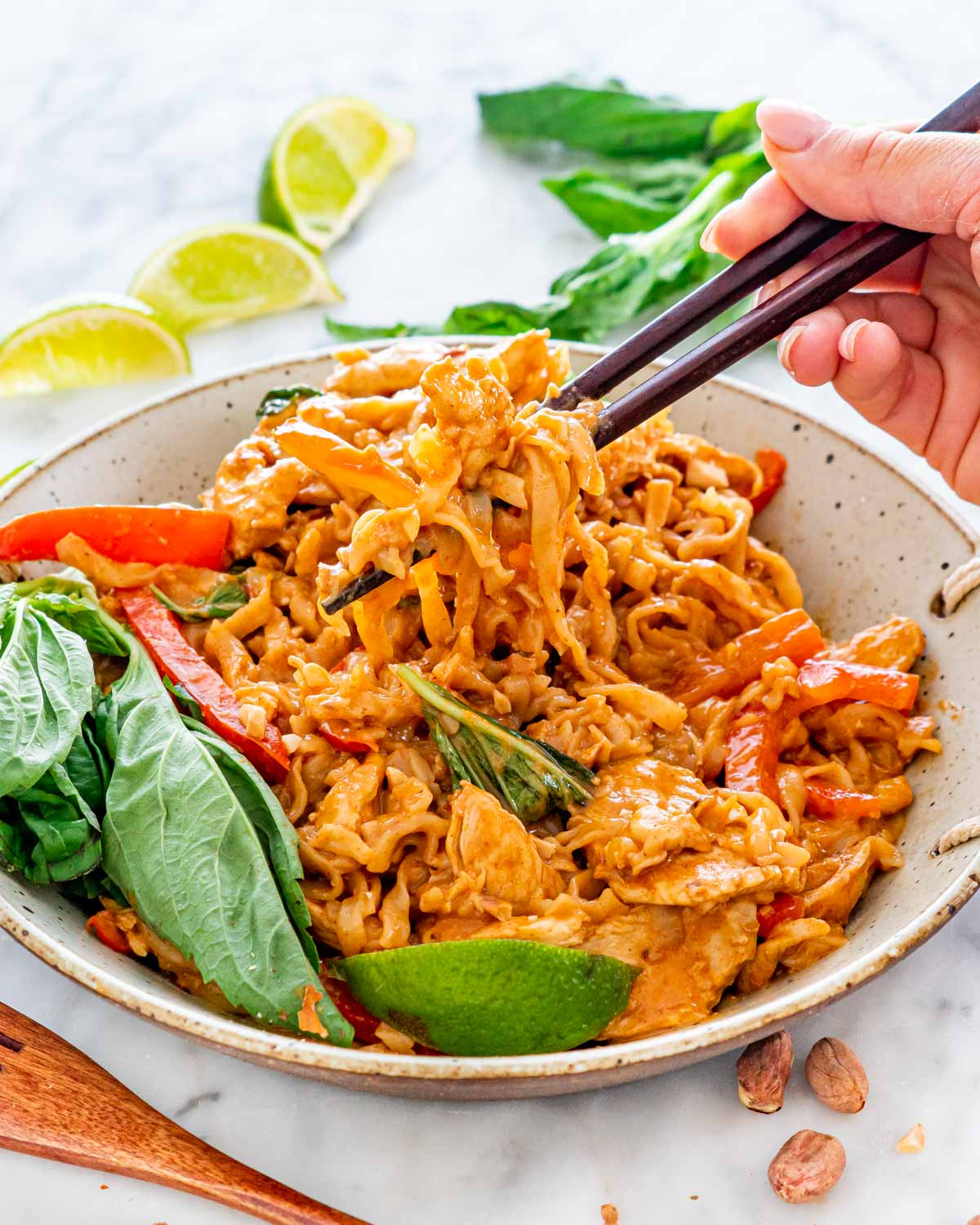 a bowl with spicy peanut noodles with chicken and garnished with basil and lime wedges