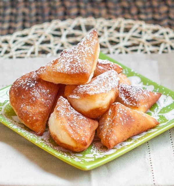 a plate of mandazi african donuts dusted with powdered sugar