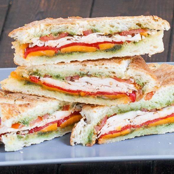Turkey Pesto Paninis cut in half, stacked on top of each other exposing the ingredients.