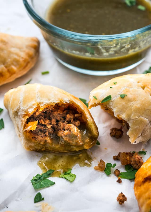 a beef empanada dunked in salsa verde and cut in half