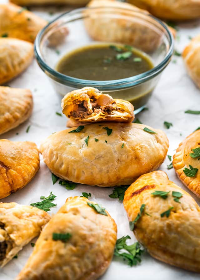 finished beef empanadas with a bowl of salsa verde garnished with cilantro