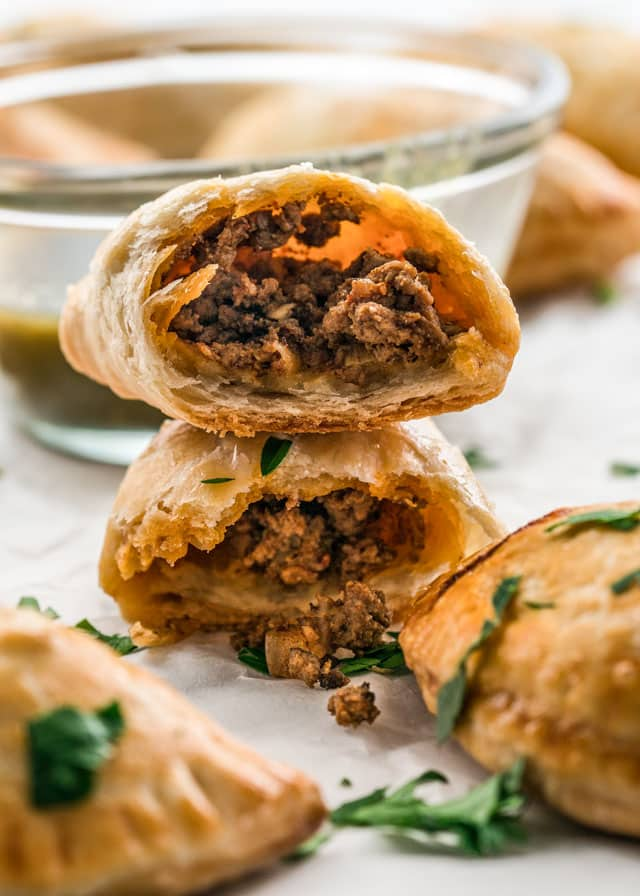 beef empanadas stacked and cut in half with a bowl of salsa verde