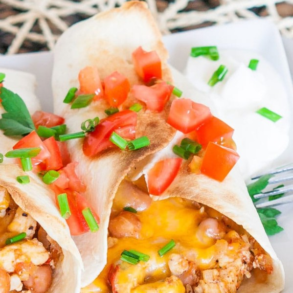 chicken burritos on a plate with sour cream