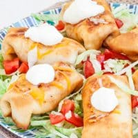 chicken chimichangas topped with a dollop of sour cream on a plate with shredded lettuce and chopped tomatoes