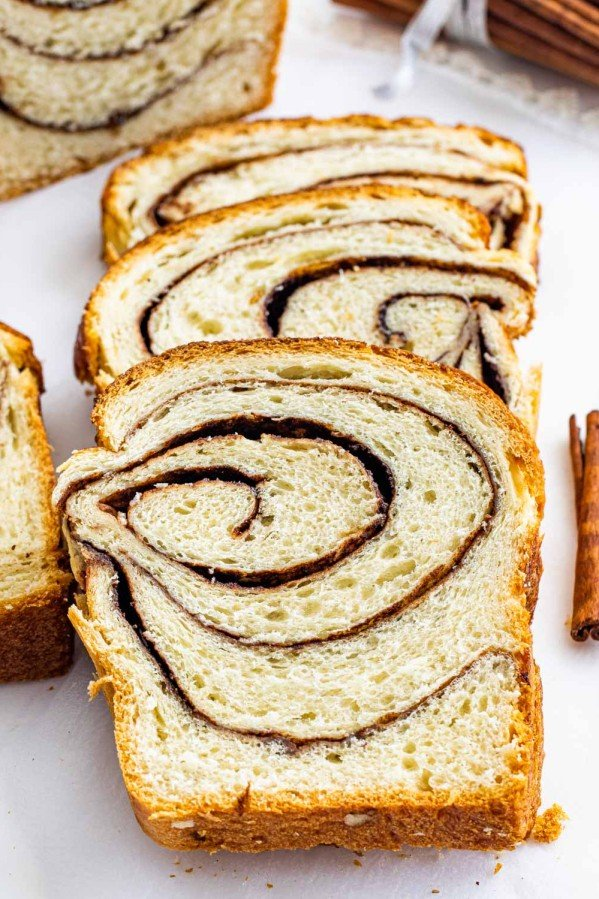 a few slices of freshly baked cinnamon bread next to a couple cinnamon sticks.