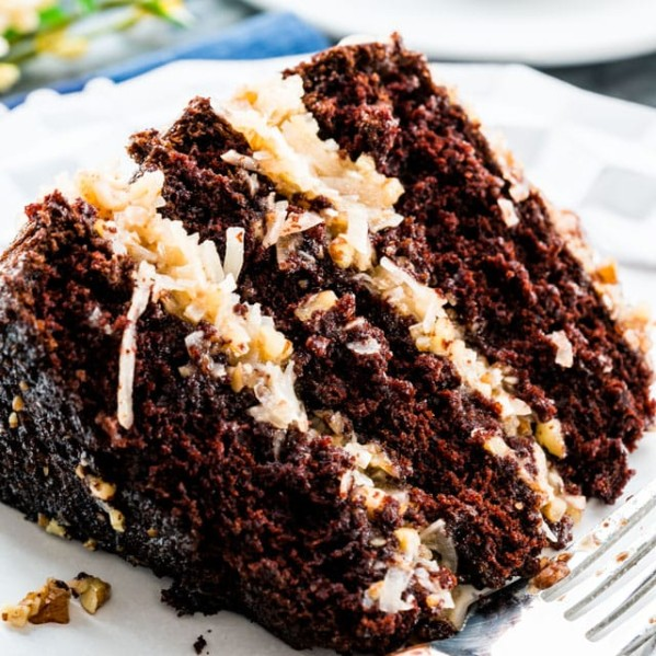 side view shot of a slice of german chocolate cake on a plate with a fork