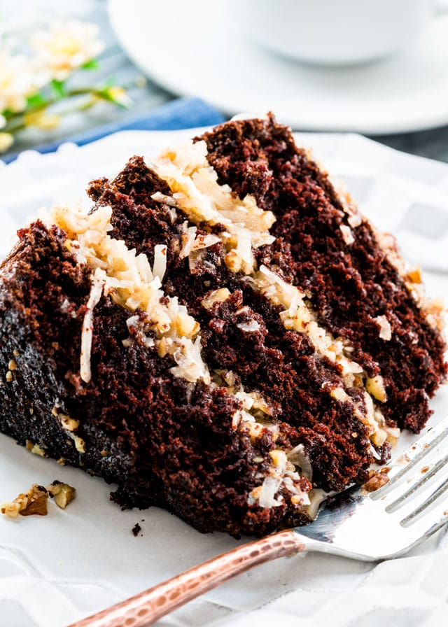 a slice of chocolate cake with layers of coconut frosting on a plate with a fork