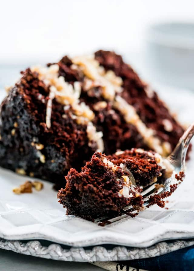 a fork taking a bite from a chocolate cake with coconut frosting