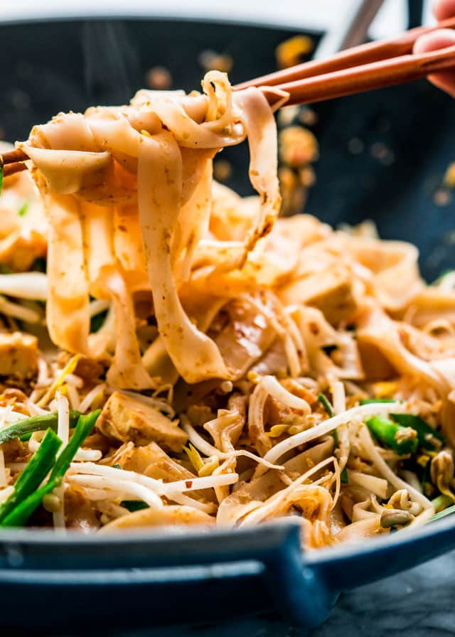 chopsticks lifting noodles out of a wok full of pad thai