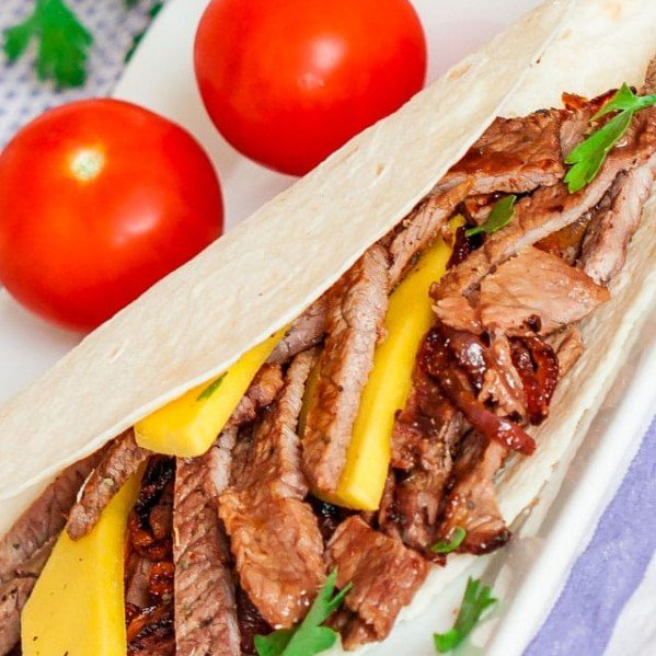 a steak and mango fajita on a plate