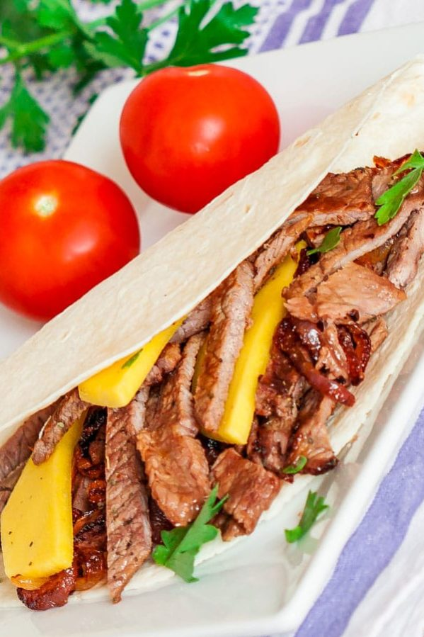 a steak and mango fajita on a plate