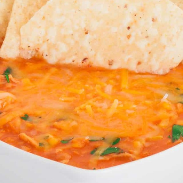 a bowl of chicken nacho soup with tortilla chips stuck in it