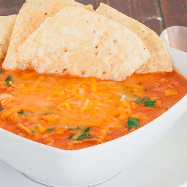 A bowl of Chicken Nacho Soup with tortilla chips sticking out