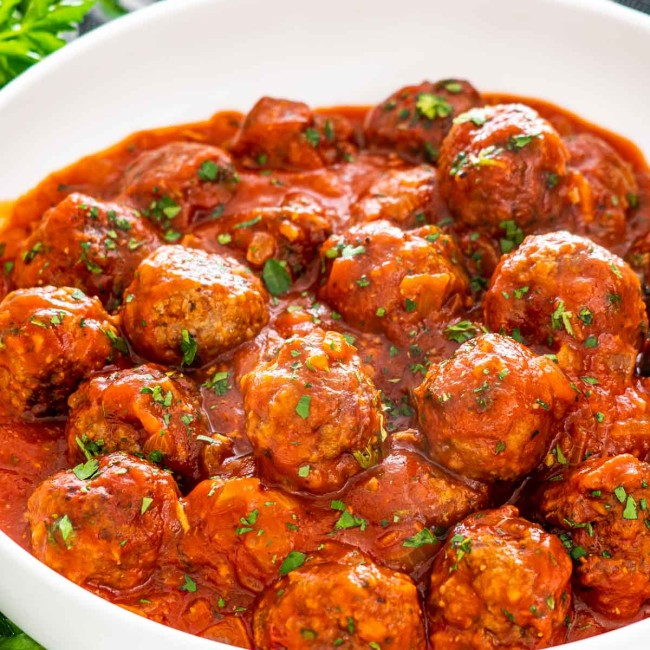 italian meatballs with sauce in a white bowl.