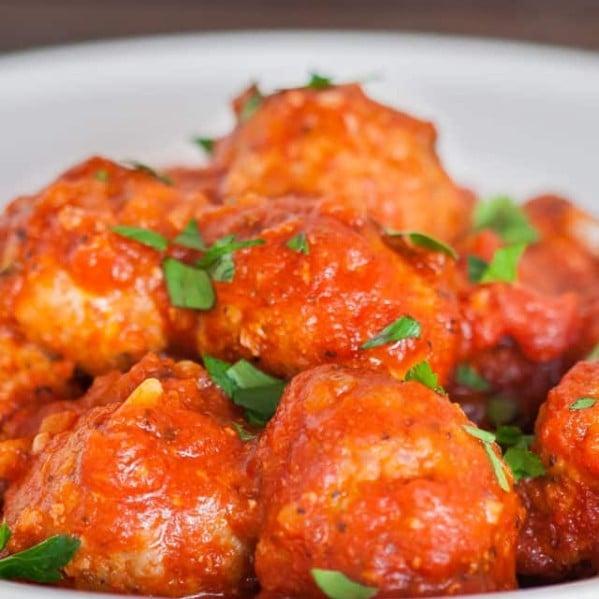 close up shot of a bowl full of italian meatballs with marinara sauce