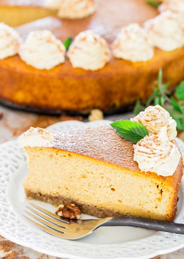 a slice of pumpkin ricotta cheesecake topped with pumpkin whipped cream on a white plate