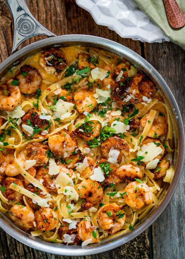 overhead of a skillet filled with fettuccine and shrimp, topped with parmesan and parsley