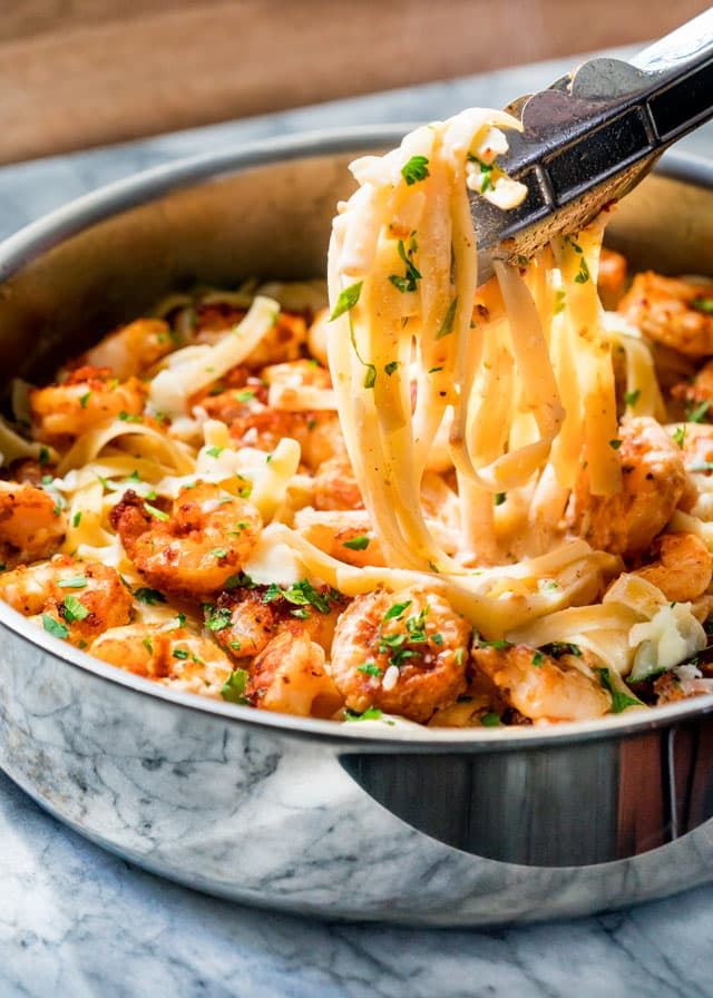tongs holding fettuccine above a skillet full of shrimp and pasta