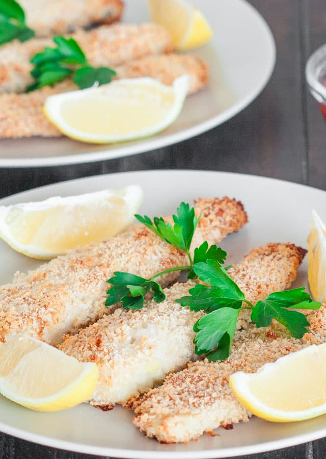 Lemony Tilapia Fish Sticks on a plate with lemon wedges as garnish
