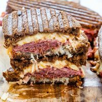 A reuben sandwich cut in half and stacked with the centers exposed