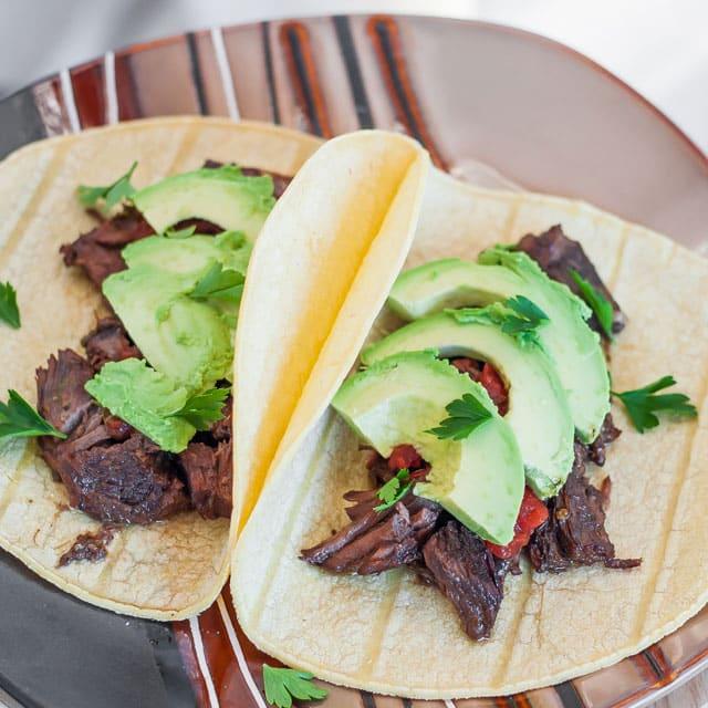 Beef Carnitas Tacos topped with sliced avocado and cilantro
