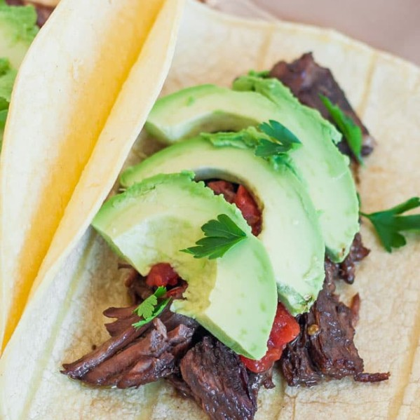 beef carnitas tacos topped with sliced avocado on a plate