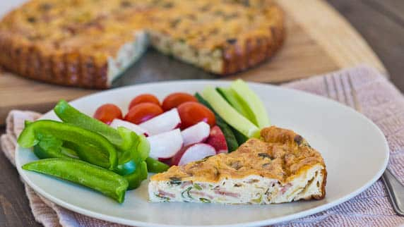 a slice of leek and turkey bacon quiche on a plate with raw veggies