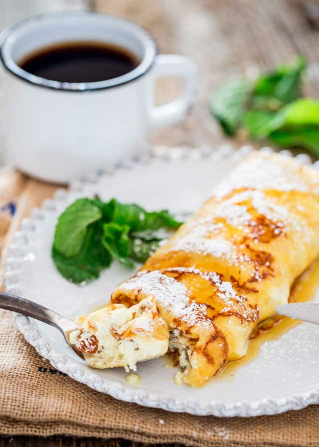 Homemade crepes stuffed with ricotta and topped with maple syrup