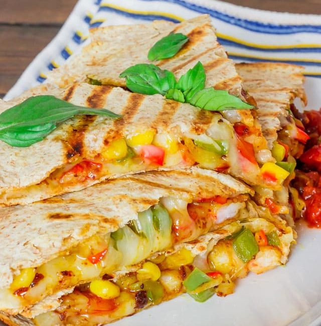 sliced shrimp fiesta quesadilla on a plate with salsa