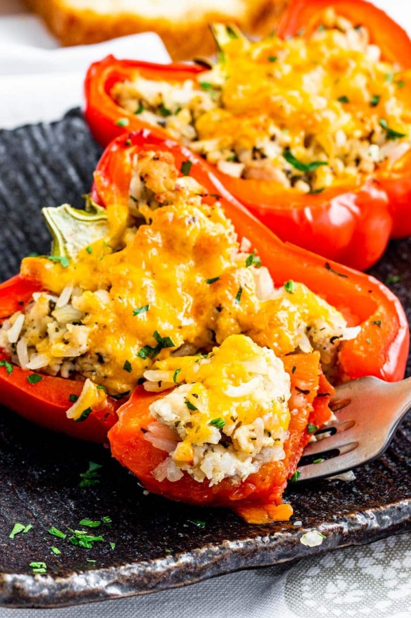 two stuffed pepper halves on a black plate with a fork holding a bite