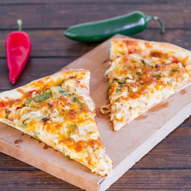 Two slices of Chicken Fajita Pizza on a cutting board