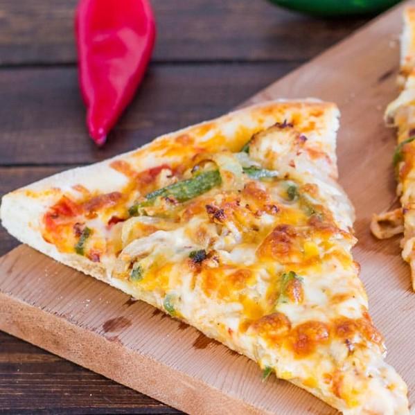 a slice of chicken fajita pizza on a wooden cutting board