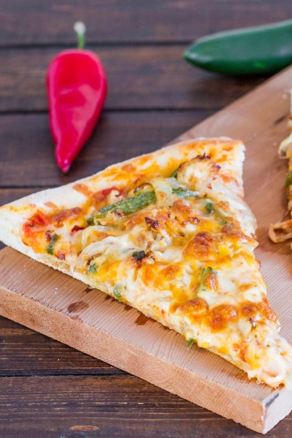 a slice of chicken fajita pizza on a wooden cutting board