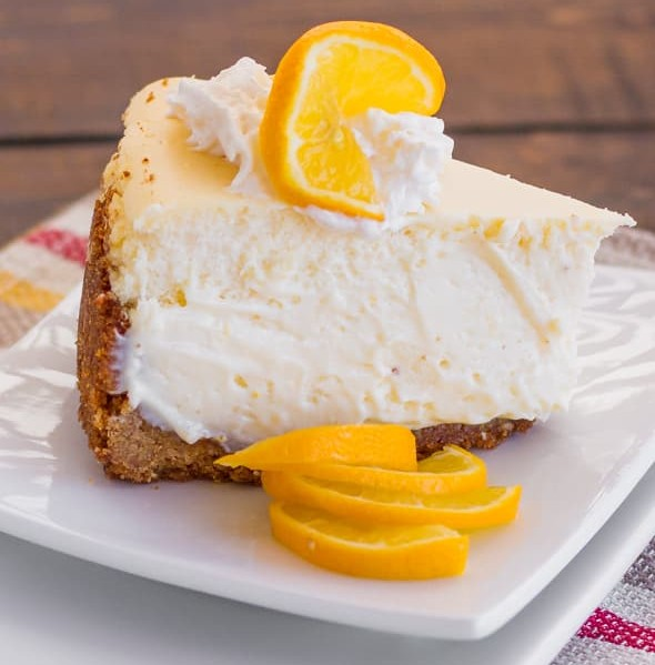 a slice of meyer lemon cheesecake garnished with meyer lemons