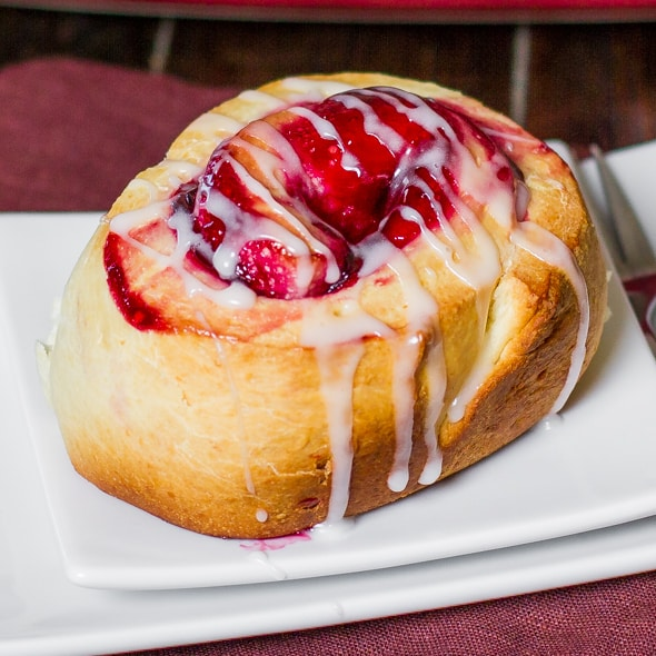 a cherry roll drizzled with icing on a plate