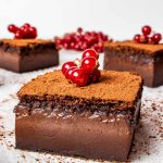 chocolate magic cake slices sprinkled with cocoa powder and garnished with garnish.