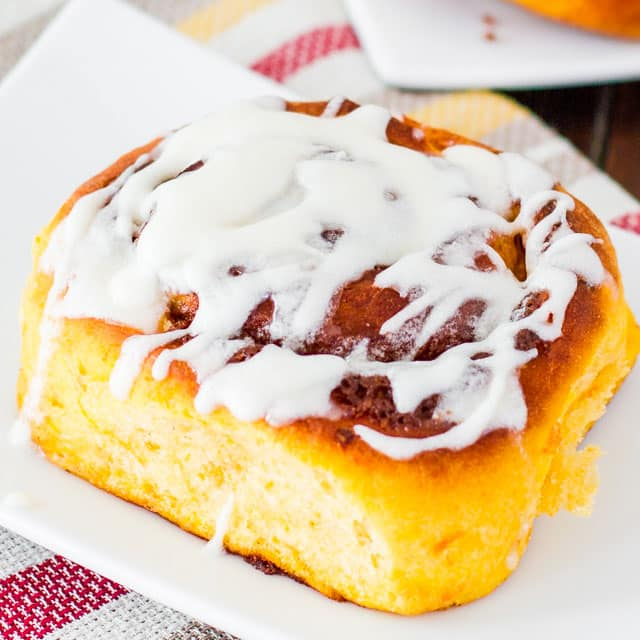 sweet potato cinnamon roll on a plate drizzled with lots of icing