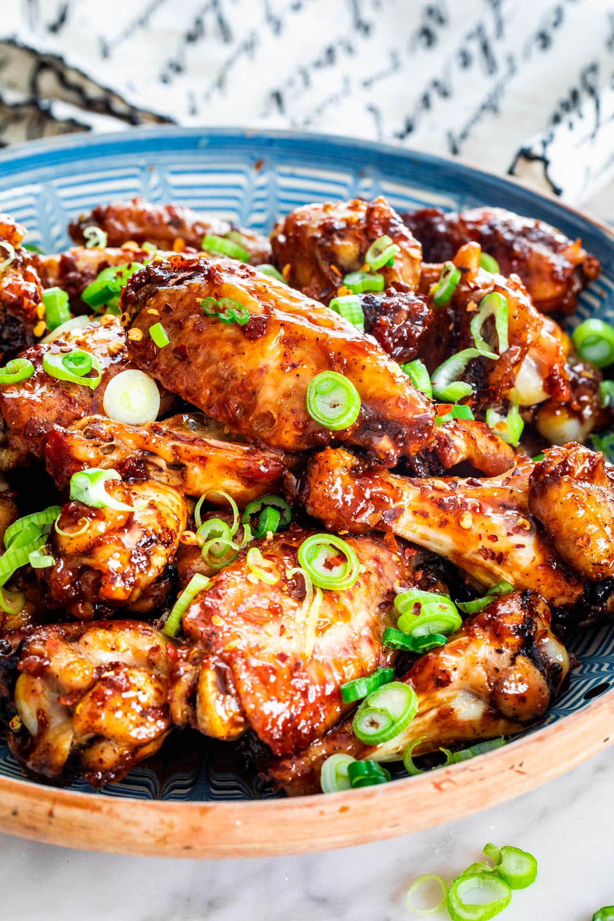 Honey Garlic Chicken Wings in a blue bowl garnished with green onions