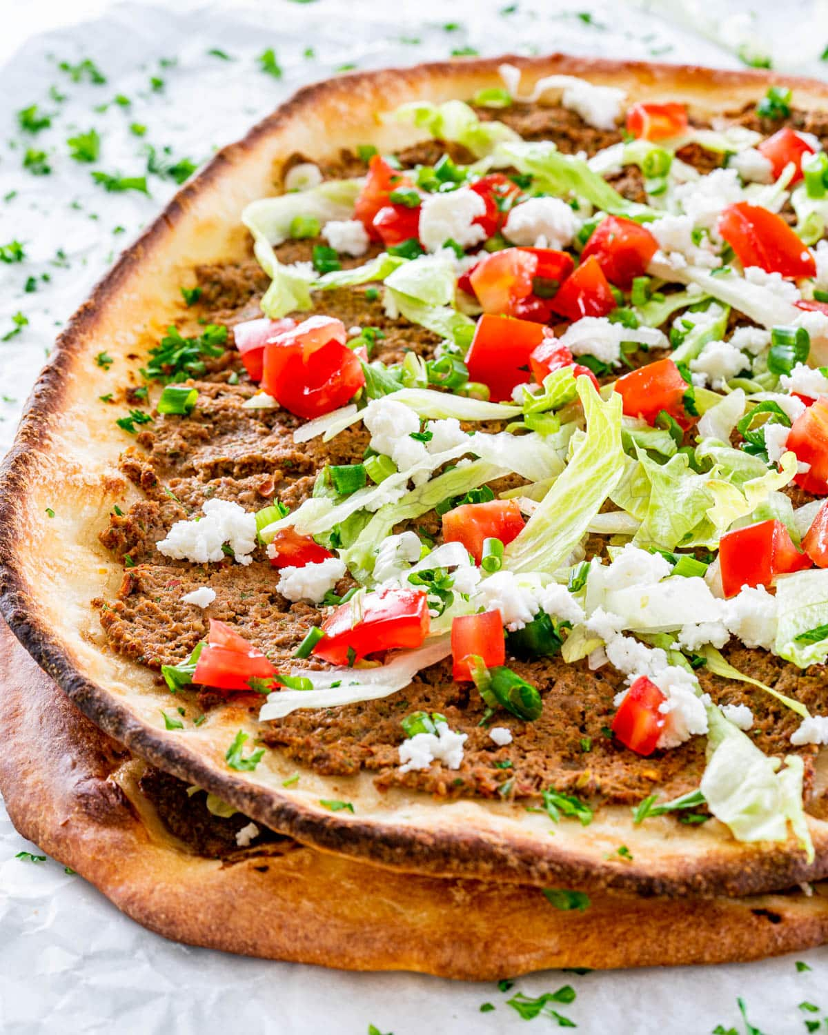 two lahmacun pies stacked garnished with lettuce, tomatoes and feta cheese