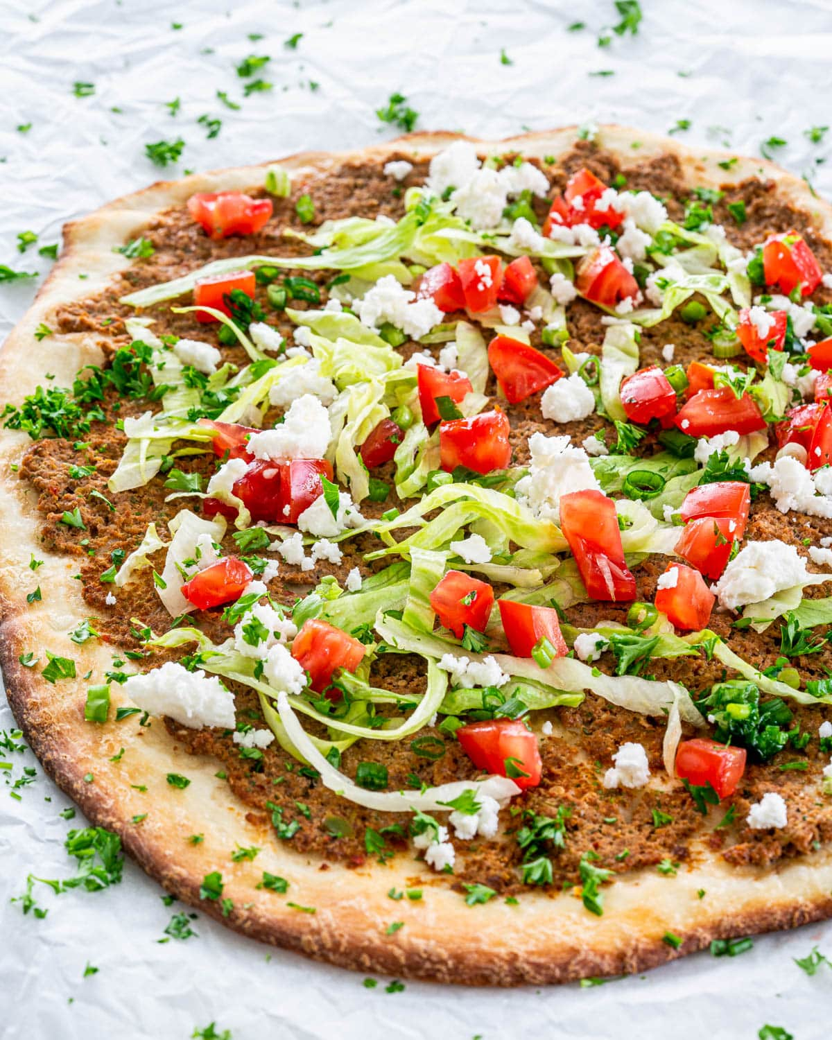 a lahmacun topped with lettuce, tomatoes and feta cheese